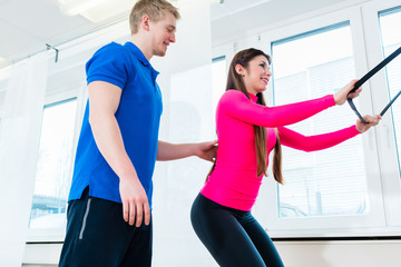 Athlete using workout equipment in health club and getting assistance by her physiotherapist