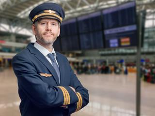 Pilot in der Uniform mit goldenen Streifen und Kappe kreuzte seine Arme beim Stehen im Flughafen Fototapete