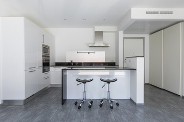 Modern white kitchen with island and stools