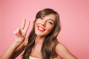 Photo of cheerful pretty woman 20s with long brown hair smiling and showing victory sign at camera while taking selfie on mobile phone, isolated over pink background