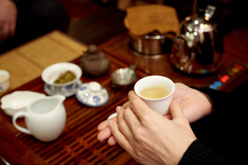 A white cup with green tea in the hands of a girl.
