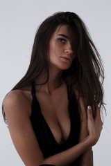 Brunette in black on white background.Tanned brunette.Portrait of brunette with beautiful godly.Portrait of a beautiful girl.Beautiful exotic young woman.Fashion photo of beautiful brunette woman.