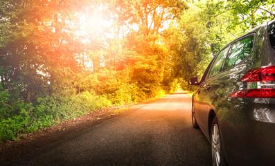autobobile su una strada di campagna al tramonto