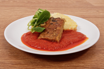 Tempeh with tomato sauce and dumplings on a table
