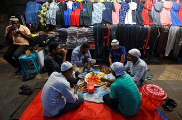 Muslim vendors eat Iftar (breaking fast) meals in front of their garment shops at a market, during the holy fasting month of Ramadan, in Kolkata
