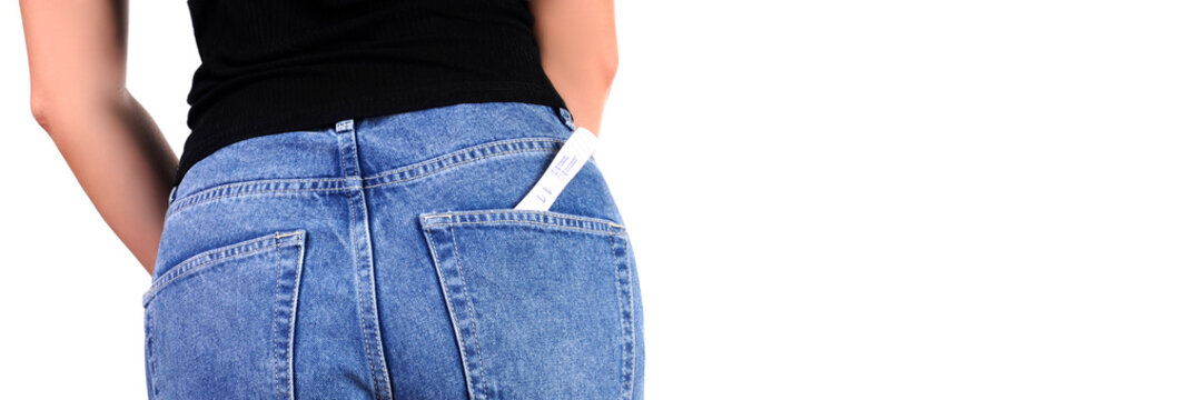 Woman with pregnancy test in pocket jeans
