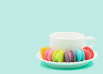 Colorful macaron cookies with tea cup on pastel background, copy space.