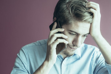 Stressed young businessman talking on mobile phone