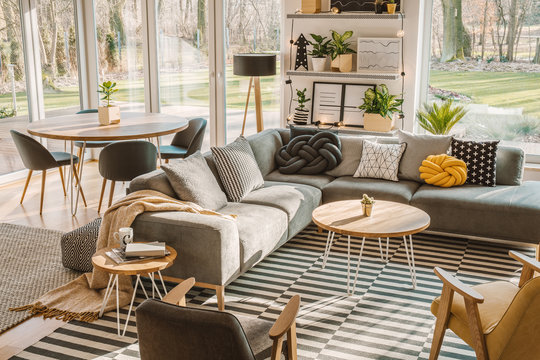 High angle view of a stylish, nordic living room interior with a wooden dining table, gray sofa and view on terrace and backyard