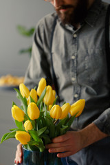 Close-up of man in grey shirt putting yellow tulips into vase