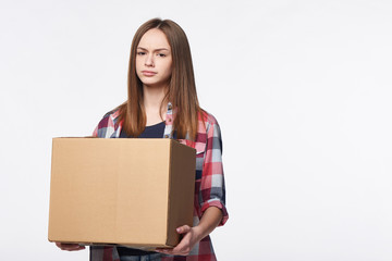 Discontent woman holding cardboard box frowning brows, over white background