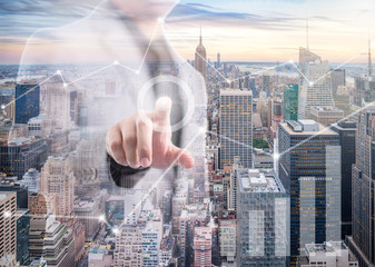 Businessman pointing his finger and touch the screen with financial info-graphic and cityscape foreground