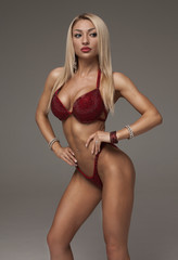 Sexy athletic woman in red bikini showing muscles on grey background. Copy space