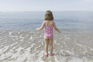 Back view of little girl standing at seafront