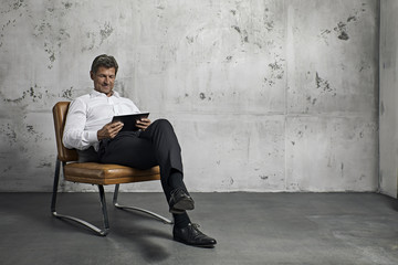 Portrait of mature man using tablet computer in front of concrete wall