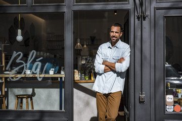 Smiling man standing at entrance door of a cafe