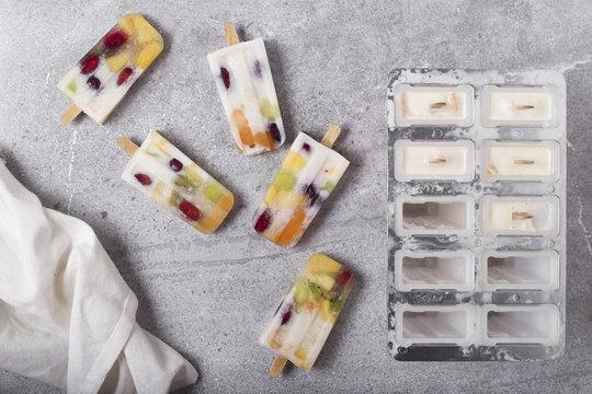 Homemade fruits and yogurt ice lollies on marble