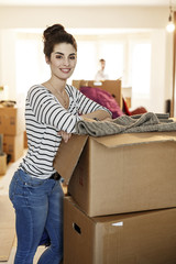Young woman moving house, unpacking cardboard boxes