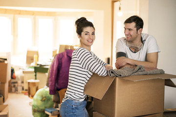 Happy couple moving house, standing by cardboard box