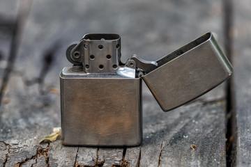 Old metal gasoline lighter on a vintage wooden table