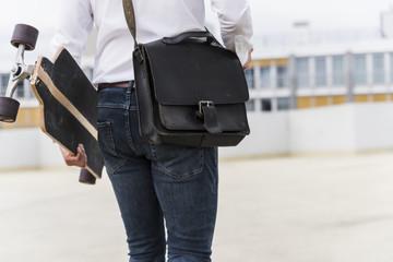 Businessman with and skateboard walking at parking garage