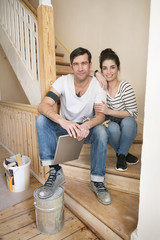 Young couple refurbishing new home, sitting on stairs using digital tablet