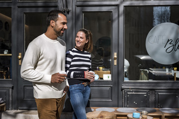 Man and woman with takeaway cups walking outside a cafe