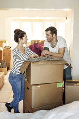 Young couple moving house, unpacking cardboard boxes