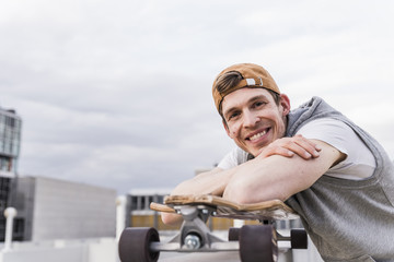 Portrait of smiling man with skateboard leaning on a wall