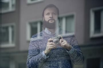 Mann mit Kamera hinter einer Glasscheibe,