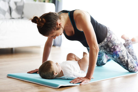 Mother with baby exercising on yoga mat at home
