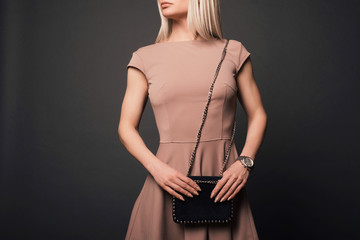 Close-up of unrecognizable woman with beautiful trendy manicureholding small black fancy handbag.