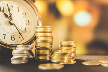 money and time concept with stack of coin and clock on table over blur gold background