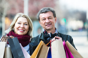 Mature spouses with shopping bags outdoor.
