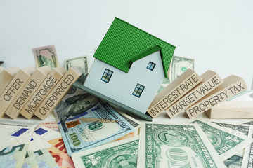 The causes of the real estate crisis with with falling house on cash banknotes