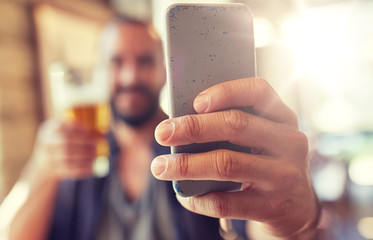 people, leisure and technology concept - close up of man with smartphone drinking beer and taking selfie at bar or pub