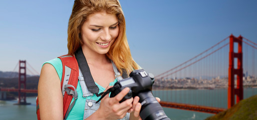 travel, tourism and photography concept - happy young woman with backpack and camera photographing over golden gate bridge in san francisco bay background