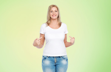 body positive, plus size and people concept - happy woman in white t-shirt pointing fingers to herself over lime green background