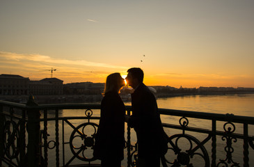 Couple in love is standing on the liberty bridge over the river Danube in Budapest. Sunrise in the big city. Dark silhouettes of man and woman holding hands in urban landscape. Sun kiss.