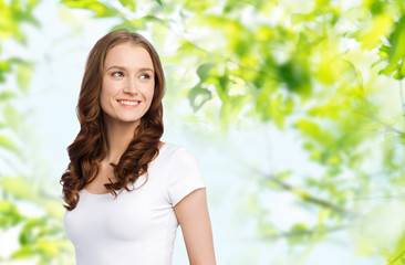body positive and people concept - happy woman in white t-shirt over green natural background