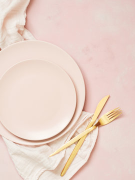 Top view of empty ceramic plates and golden cutlery on pastel pink background