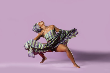 Photo Blinds Dance School Beautiful African Black girl wearing traditional colorful African outfit does a dramatic aggressive crouching dance move against a colorful purple background