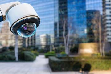 security CCTV camera or surveillance system with buildings on blurry background