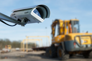 security CCTV camera or surveillance system with industrial site on blurry background