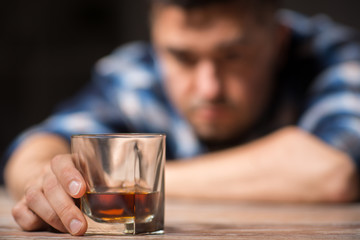 alcoholism, alcohol addiction and people concept - male alcoholic with glass of whiskey lying on table at night