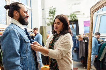 sale, shopping, fashion and people concept - couple choosing clothes at vintage clothing store
