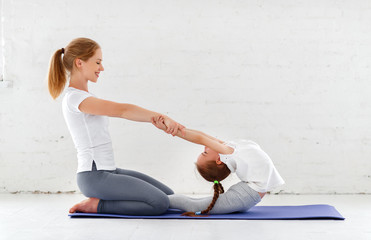 mother with child practicing yoga in lotus pose