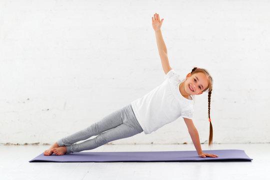 child girl doing yoga and gymnastics in gym