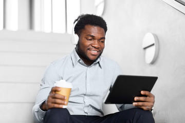 business, people and technology concept - african american businessman with headphones and tablet pc computer listening to music at office coffee break