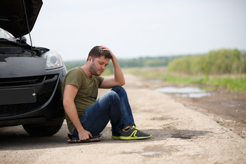 Photo of frustrated man sitting next to broken car with open hood
